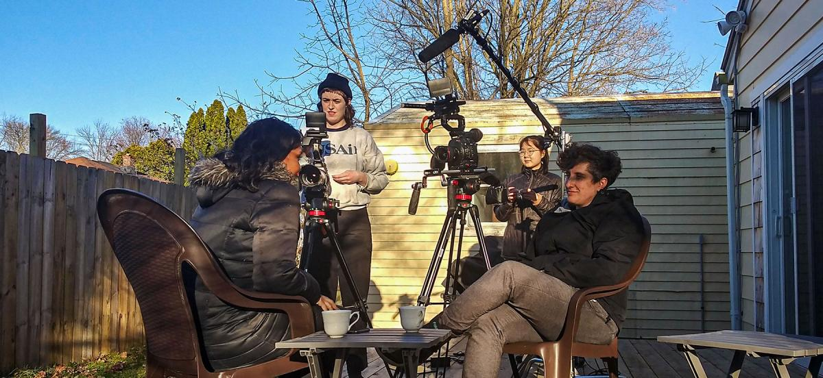 Two people in the foreground sit in chairs, conducting an interview, while two people in the background run cameras and sound equipment to capture it