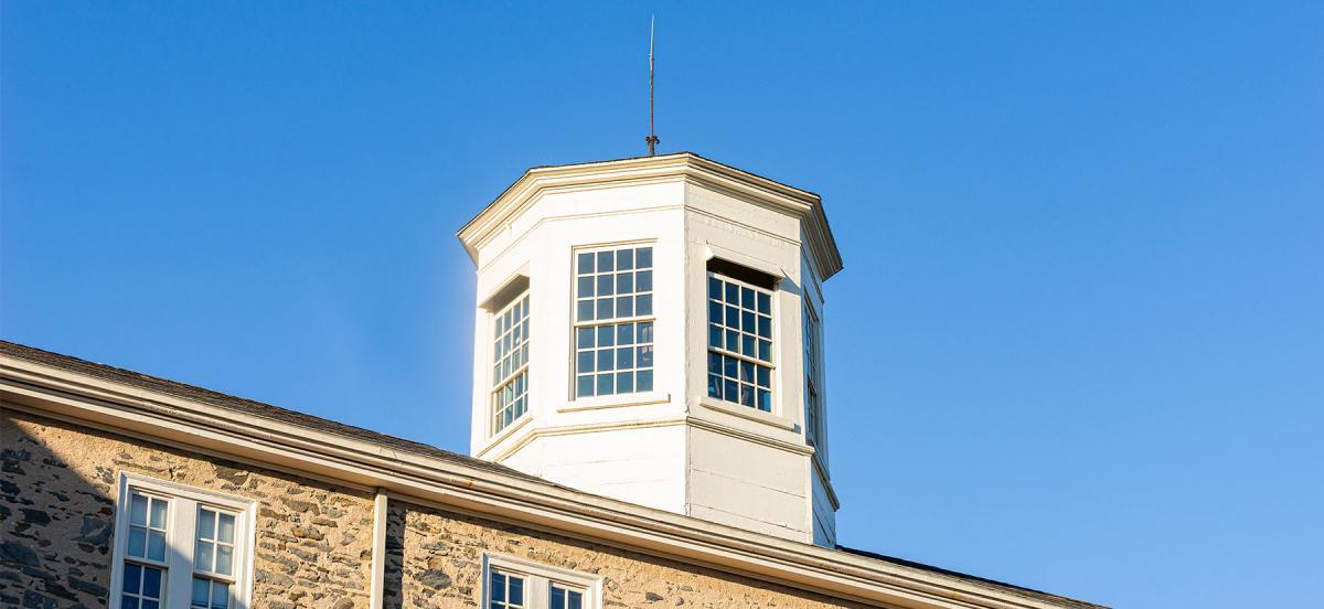 The sun shines on Founders Hall's cupola against a blue sky