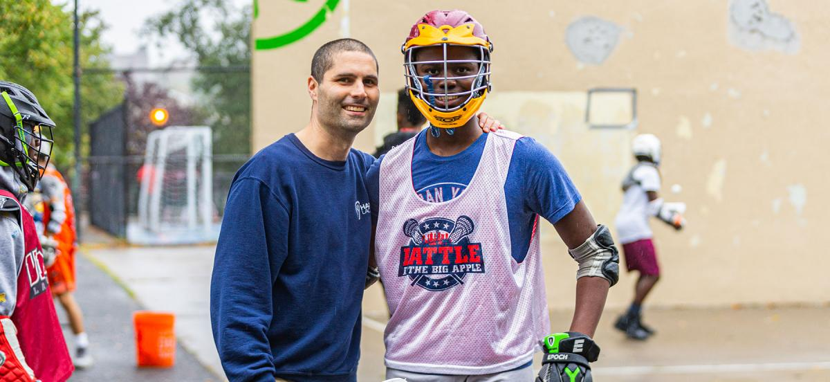Joel Censor teaches lacrosse to students on handball courts