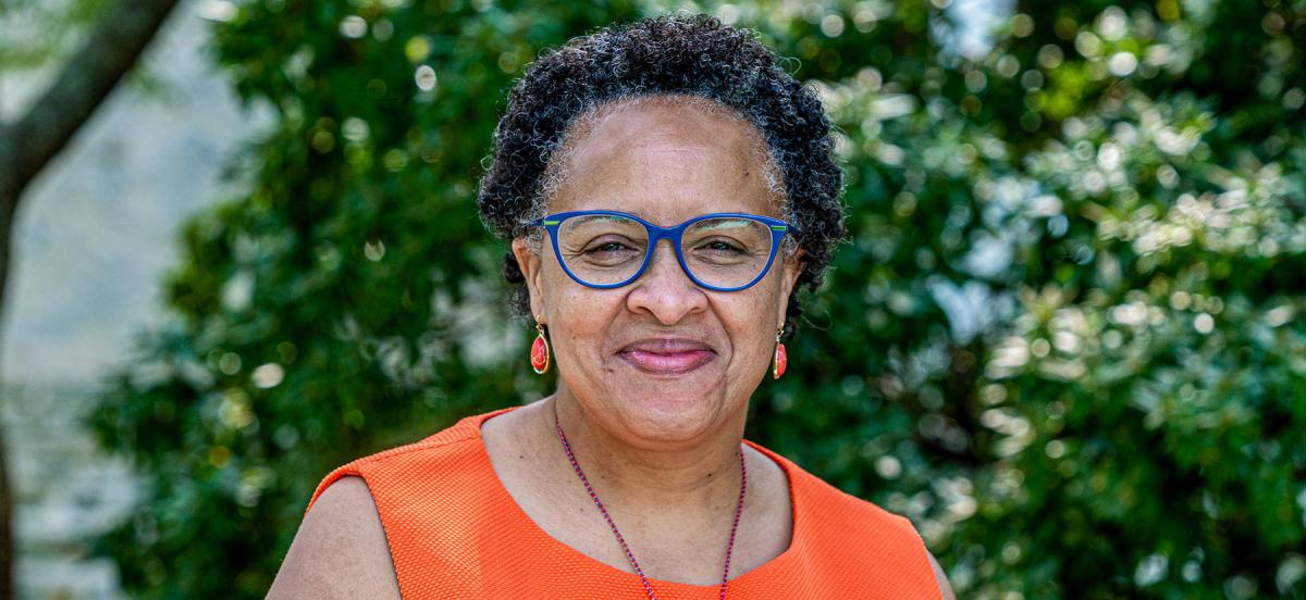 An outdoor portrait of Linda Strong-Leek, wearing glasses and an orange shirt