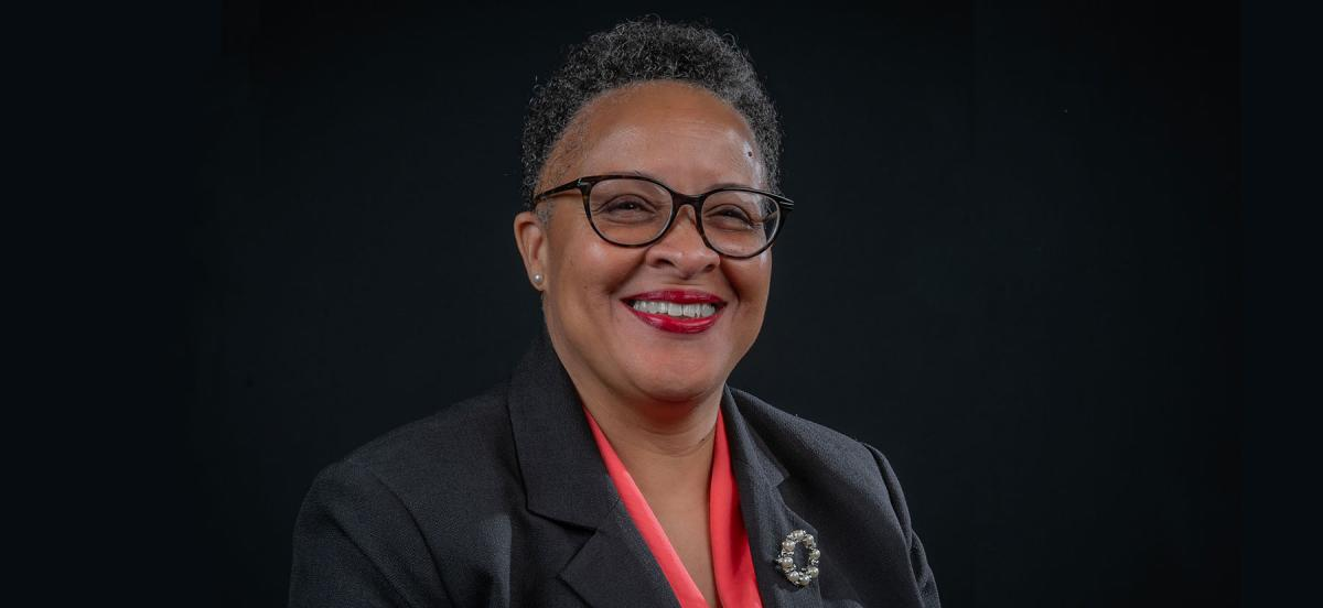 A headshot of Linda Strong-Leek smiling and wearing a black jacket and red blouse