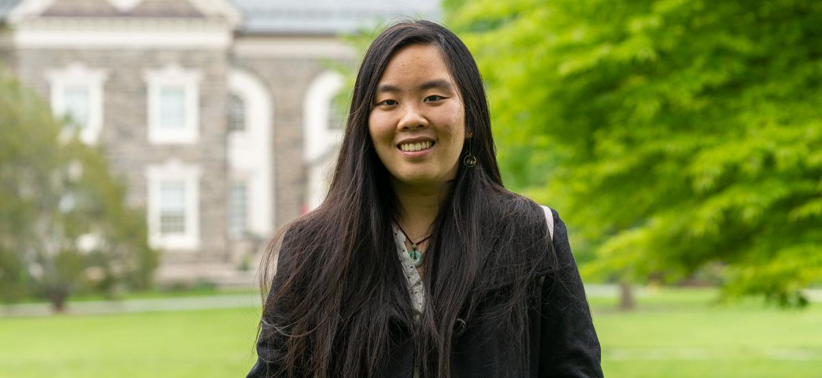 Margaret Chen wears a black jacket and a circular jade pendant necklace, standing in front of VCAM on Founders Green