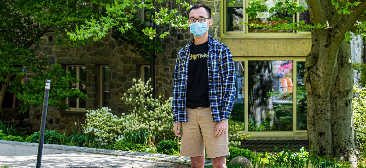 Theo Bien wears a mask in front of his dorm.