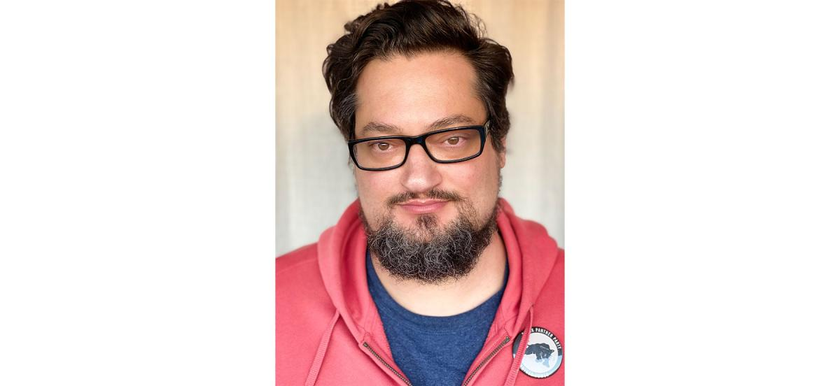 A headshot of Will Berson '98, wearing glasses and a red hoodie