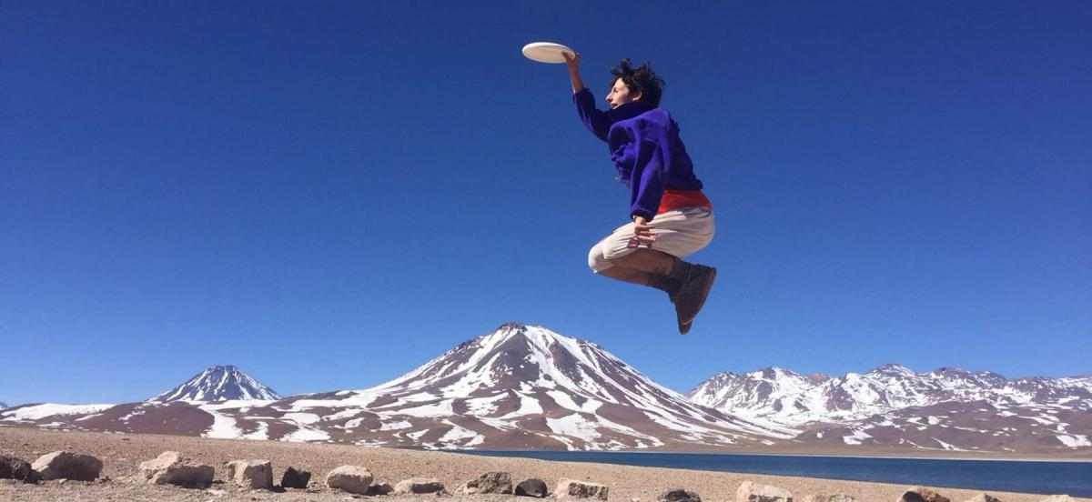 Student jumping in the air catching a frisbee with mountains behind him