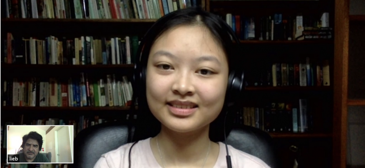 A screen shot of zoom call with a student in a light pink shirt with books in the background. In the corner, there is the view of a man.