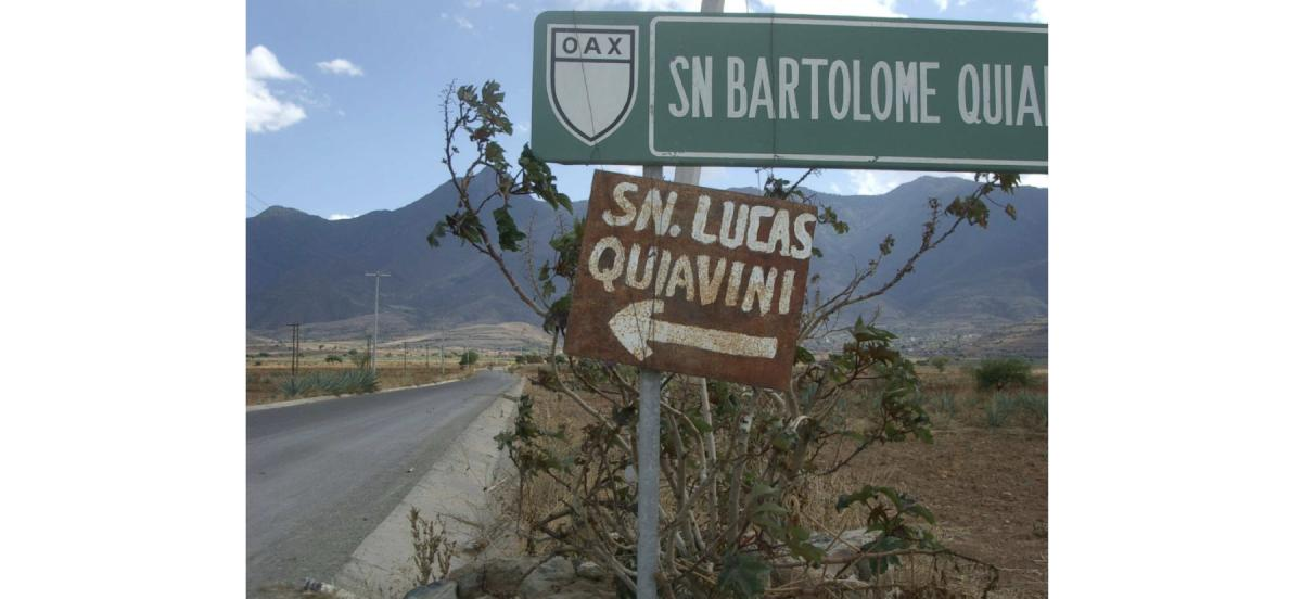 a photo of a road leading toward some mountains with two street signs in the foreground, one official and one handpainted