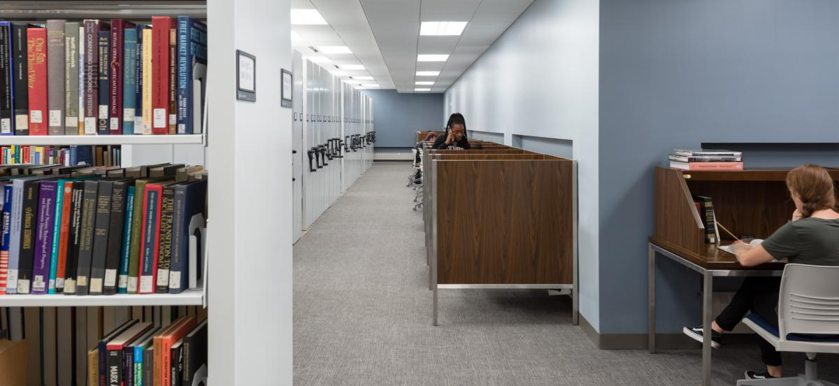 Stacks and carrels in Lutnick level 0, with students working at carrels.