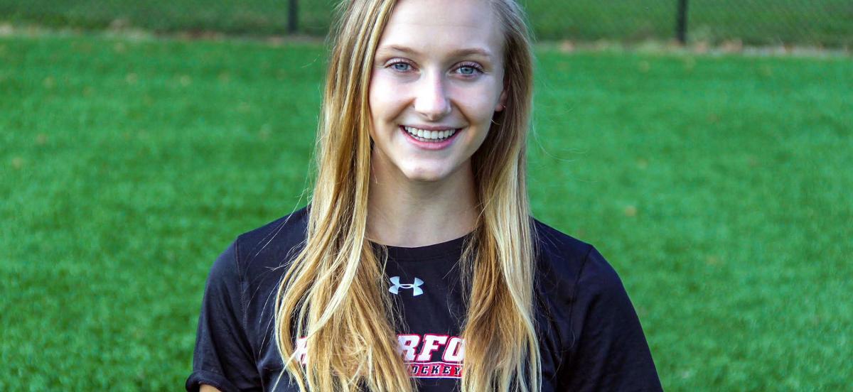Headshot of Julie wearing a Haverford Field Hockey shirt on a green field.