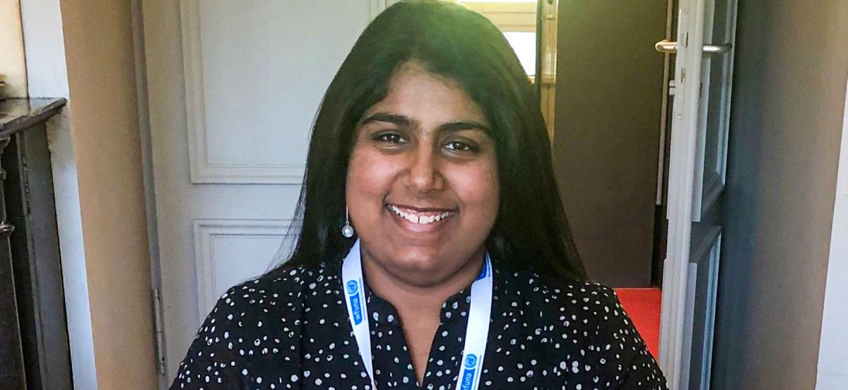 Saumya smiles, wearing a black dress with white dots and a landyard around her neck.