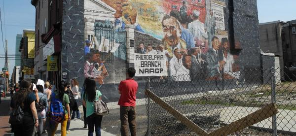 Group of students view one of Philadelphia's murals.