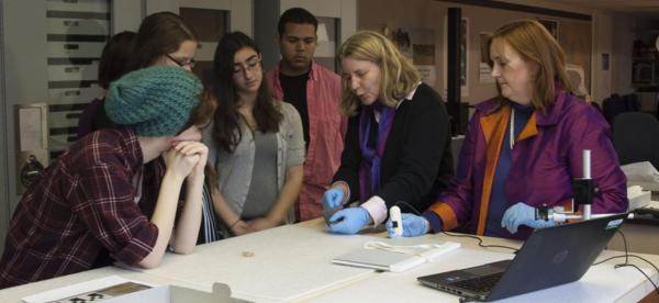 A group of students are instructed by a professor on an archeological item.