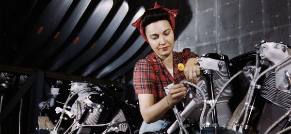 a WWII-era woman working on a motorcycle