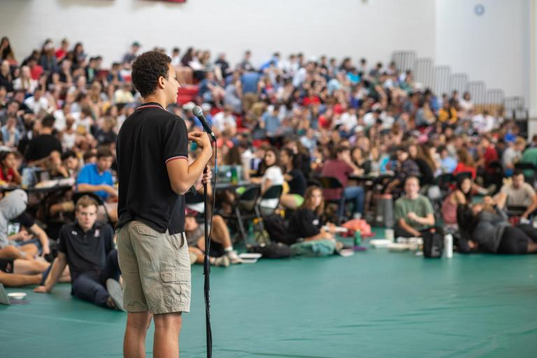 A student stands at a microphone addressing his peers during Plenary