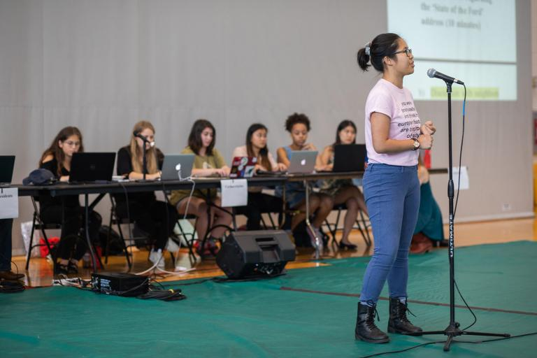 A student stands at a microphone in front of the student body