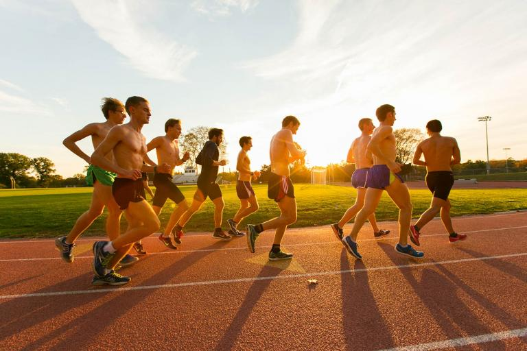 Students run on the track while the sun sets