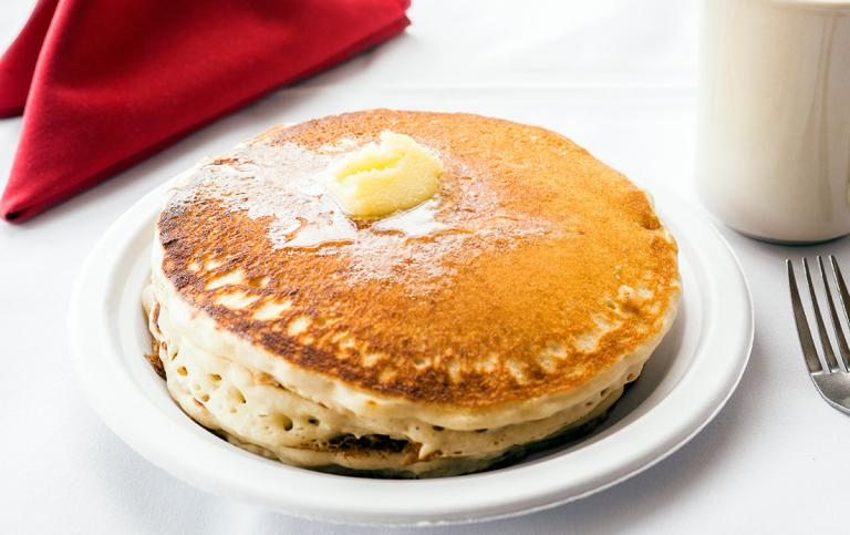 A mouthwatering stack of fluffy pancakes with butter on top