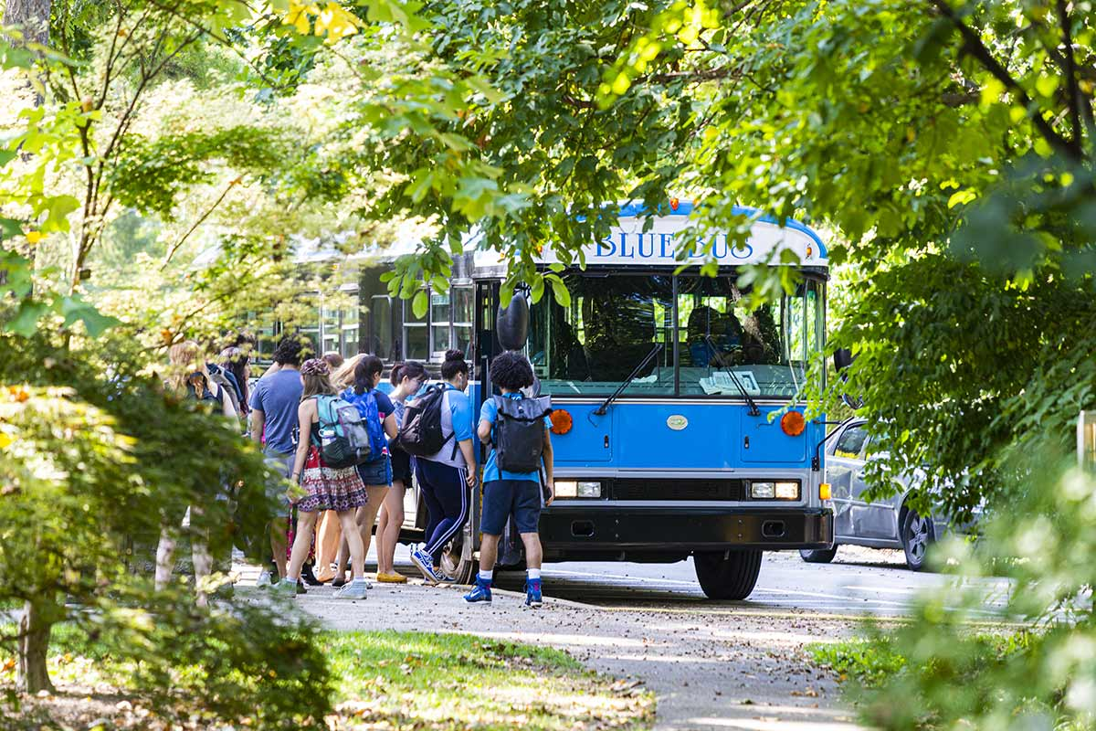 students approaching the blue bus to head to bryn mawr college